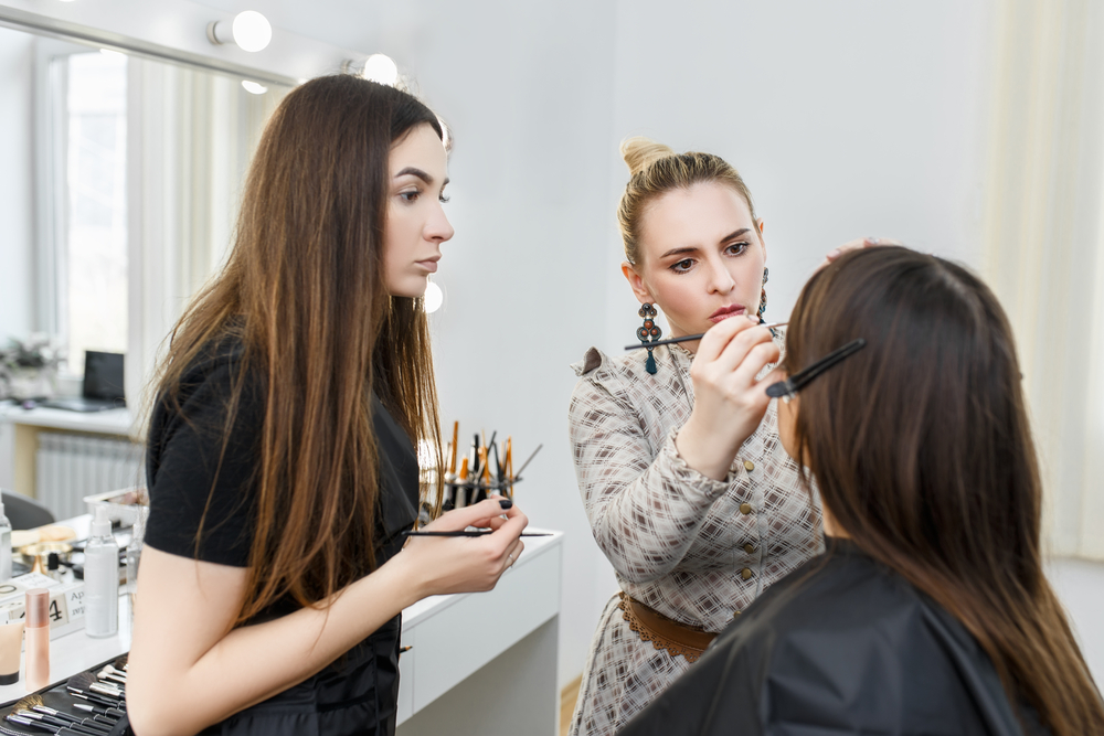 beauty school teacher showing her student how to do makeup