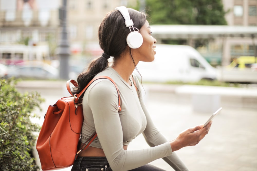 Woman with a backpack wearing headphones