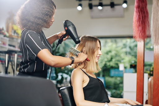 woman blow drying another woman's hair
